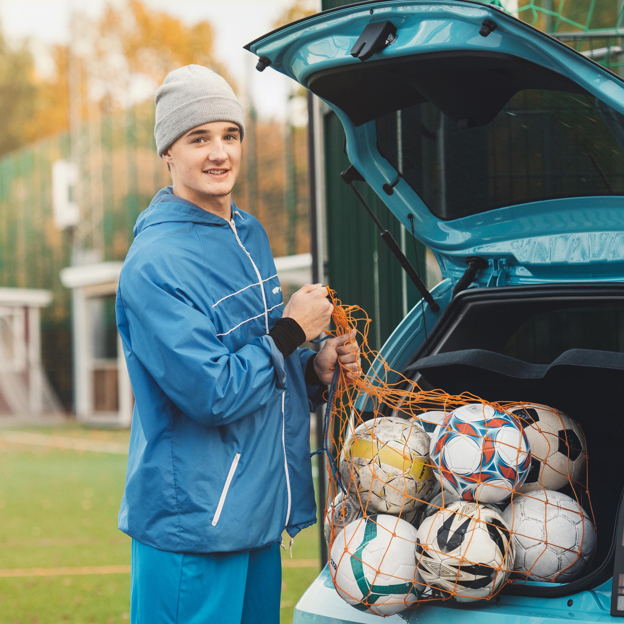 Young soccer coach with a bunch of footballs